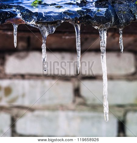 Icicles On Roof Of Barn With Brick Wall