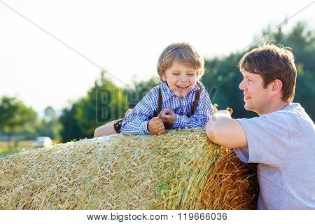 Father and little son having fun on yellow hay field in summer
