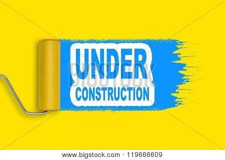 Roller painter blue stroke on yellow background with words under construction