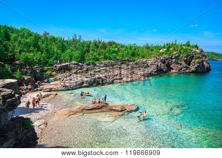 great natural rocky beach view and tranquil azure clear water with people relaxing in background