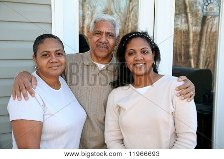 Minority family standing outside their new home