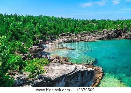 gorgeous amazing natural rocky beach view and tranquil azure clear water with people in background