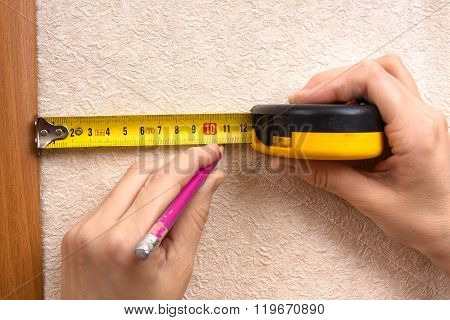 Hands Measuring Wall With Tape Measure