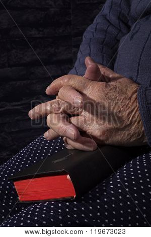Grandmother praying. Old wrinkled beautiful woman praying with bible. Spirituality.