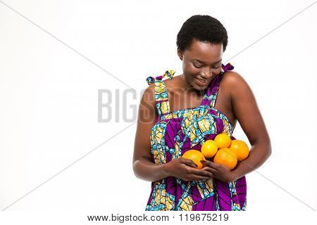 Pretty happy african american young woman in bright sundress with oranges and lemons over white background