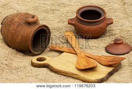brown clay pitcher,clay pot ,cutting Board and spoon with a fork