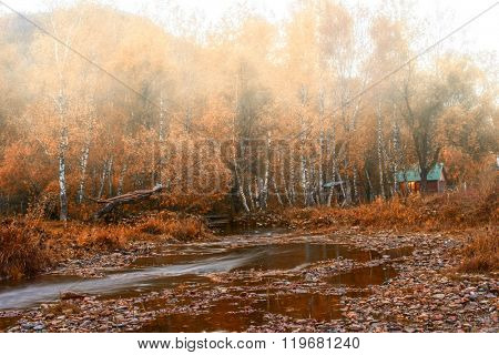 Autumn at mountain village. Morning fog at river