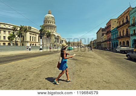 HAVANA, CUBA - June 29, 2015: A woman crosses the street with tourist map in hand near the Capitol