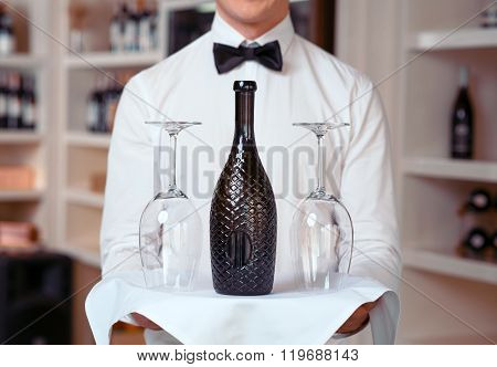 Sommelier holding tray with wine bottle