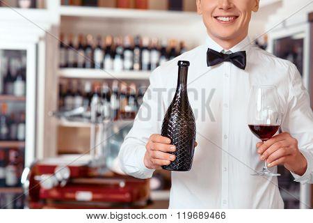 Smiling sommelier holding glass of wine