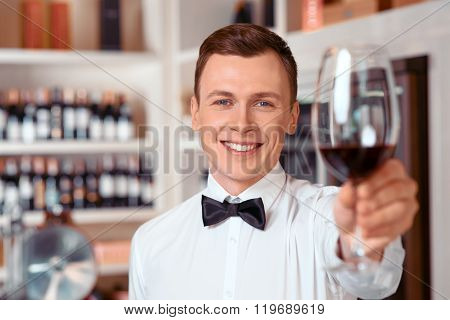 Handsome sommelier holding glass of wine