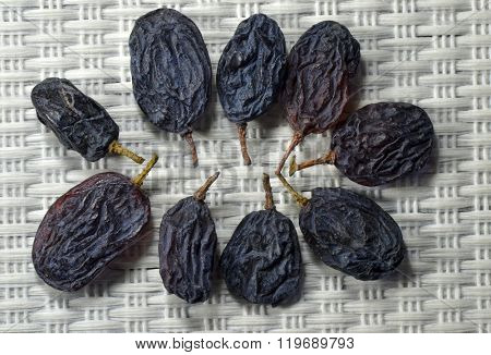 Group of dry seedless grapes on light gray mat.