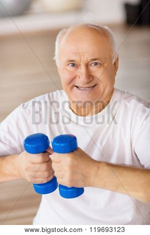 Senior man  holding weights in gym