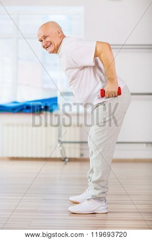 Positive aged man practicing with weights