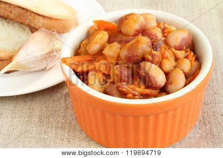 Haricot bean ragout with carrot, onion and tomato dressing in orange ceramic bowl on linen cloth