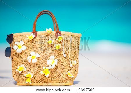 Closeup beautiful bag with frangipani flowers and sunglasses on white beach