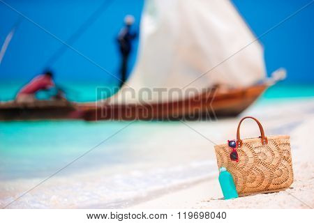 Beach accessories - straw bag, sunscreen bottle and red sunglasses on the beach
