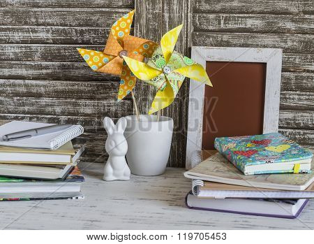Children's Home Workspace With Books, Notebooks, Notepads And Handmade Paper Pinwheels And Easter Ce