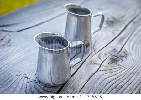 Small milk jug on old wooden table at a mountain farm in South Tyrol Italy