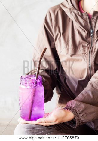 Woman Hand Holding Iced Drink In Violet Glass