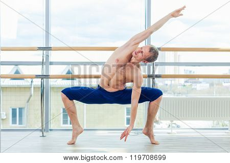 in the hall man doing stretching near Barre