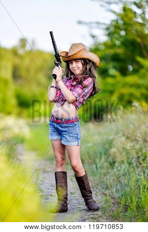 Little Girl With A Toy Gun In His Hand Standing In A Field