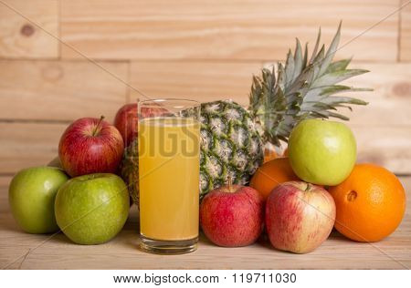 variety of fruits and orange juice on a wooden table, studio picture