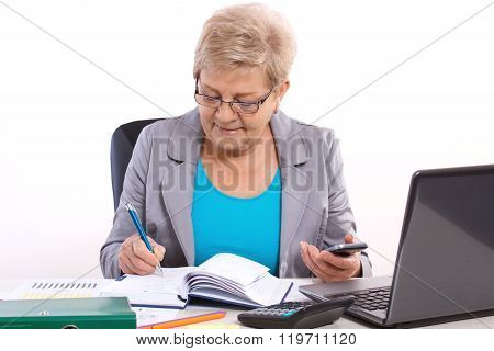 Elderly Business Woman Writing In Notebook And Working At Her Desk In Office, Business Concept