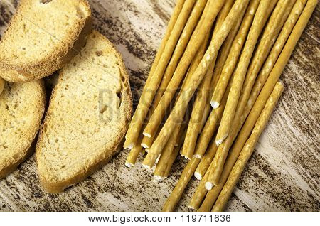 Rusks And Sweet Sticks Horizontally On  Background Of Wood.