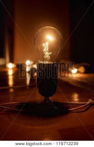 Large brushed electric incandescent lamp on the floor, against a dark background. Light in darkness.