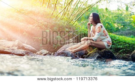 Young Woman Is Sitting On The Stone