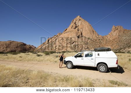 A 4x4 stands in front of the Spitzkoppe, Namibia.
