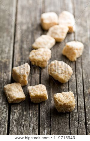 unrefined cane sugar cubes on old wooden table
