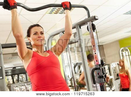 Sporty woman doing hard pull-up workout in health club.