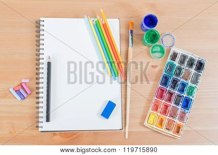 Top View Of Blank Notebook Or Notepad And Watercolour, Pencils Supplies On The Wood Background Desk