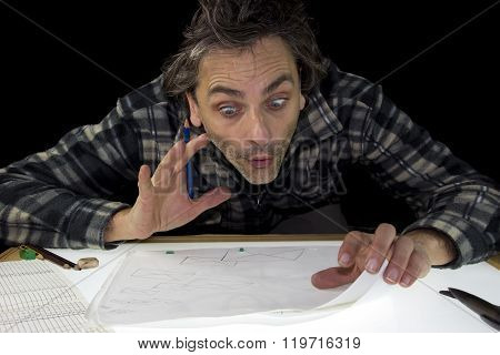 surprised man with pencil working on lightbox
