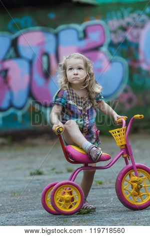 Little cyclist girl wearing checked tunic riding yellow and pink tricycle