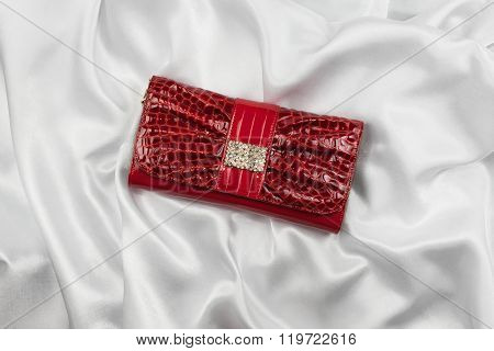 Red Lacquer Bag Inlaid With Diamonds Lying On A White Silk