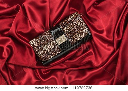 Black Lacquer Bag Inlaid With Diamonds Lying On A Red Silk