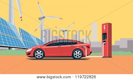 Electric Car Charging At The Charging Station In Front Of The Solar Panels And Wind Turbines