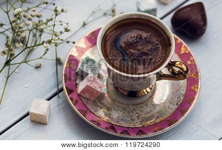 Turkish coffee with heart shaped chocolate and Turkish delights, wooden background