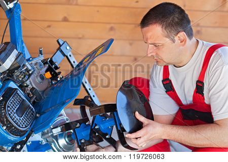 Man Installing Tilling Accessory On Agricultural Machine