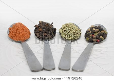 Metal spoons with spices on the white ceramic