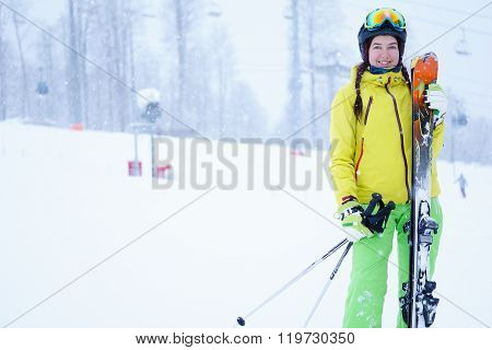 Female skier standing with skies in one hand on background beautiful mountain landscape