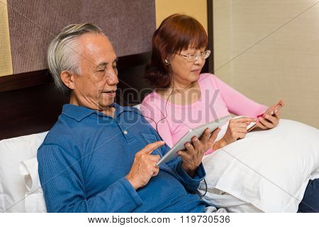 Asian Male Using Tablet In Bed