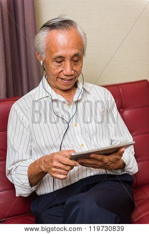 Senior Male Using Technology For Entertainment