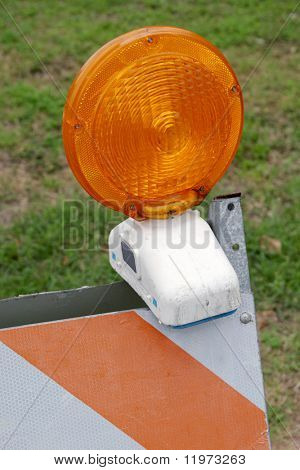 A closeup of an orange and white traffic barracade with the orange light on top. Grass in background.