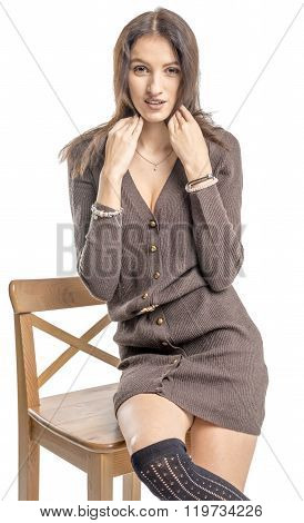 Beautiful brunette girl posing on a chair in a long sweater