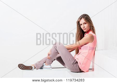 Confident girl is sitting on white background