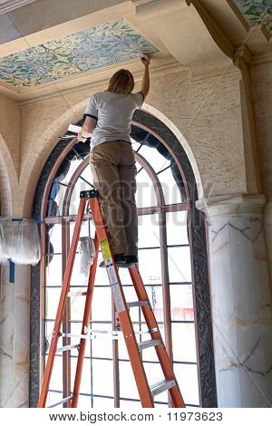 Woman on ladder restoring ceiling